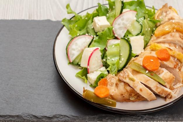 Teller mit fleisch, salat aus frischem gemüse mit gurke und rettich auf schwarzem steinbrett. ansicht von oben.