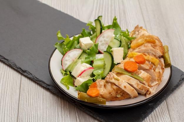 Teller mit fleisch, salat aus frischem gemüse mit gurke und rettich auf steinbrett. ansicht von oben.