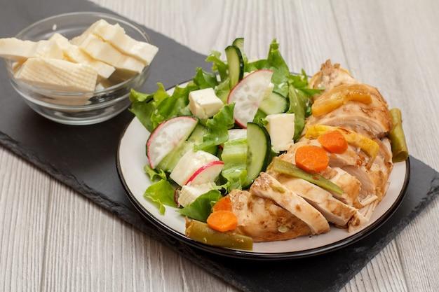 Teller mit fleisch, salat aus frischem gemüse mit gurke und rettich, glasschüssel mit käse. ansicht von oben.