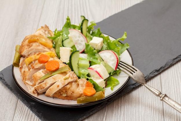 Teller mit fleisch, salat aus frischem gemüse mit gurke und rettich mit gabel auf schwarzem steinbrett. ansicht von oben.