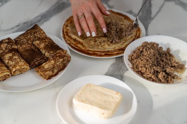 Teller mit fleisch- und quarkfüllung für pfannkuchen und die hände des küchenchefs, der das gericht zubereitet