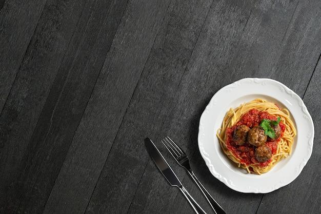Teller mit fleischbällchen spaghetti, tomatensauce und minzblatt auf dunklem holzhintergrund. platz kopieren