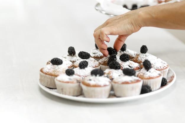 Teller mit frisch gebackenen süßen muffins. süßes gebäck, rezepte, kochen