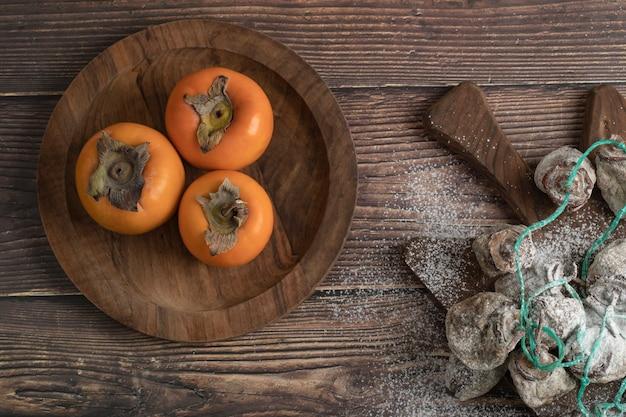 Teller mit frischem fuyu und getrockneten kakifrüchten auf holzbrett
