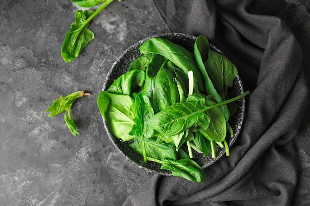 Teller mit frischem grünem spinat auf dem tisch