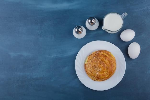 Teller mit frischem rundgebäck mit eiern und milch auf blauer oberfläche.