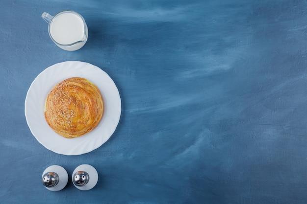 Teller mit frischem rundgebäck mit frischer milch auf blauer oberfläche.
