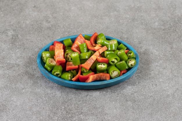 Teller mit frischem salat mit chili und paprika auf marmoroberfläche.