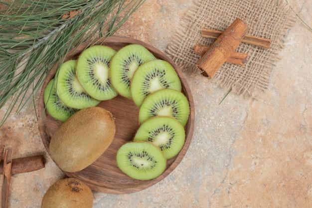 Teller mit frischen kiwi- und zimtstangen auf marmorhintergrund.