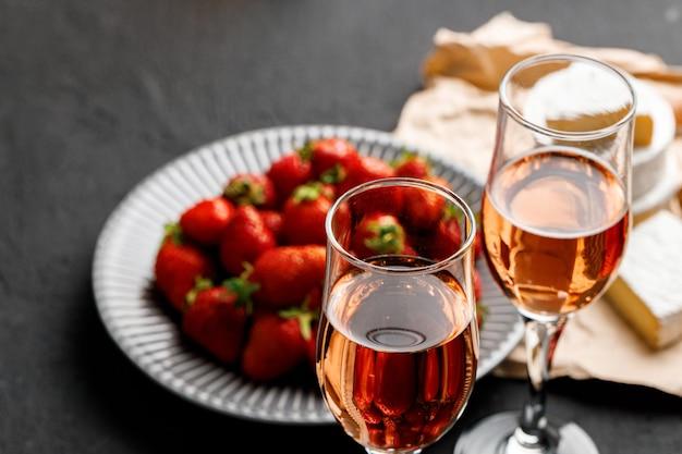 Teller mit frischer erdbeere und einem glas wein auf schwarz