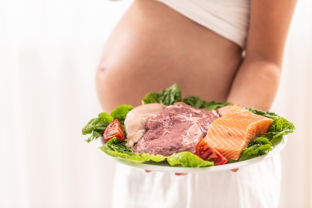 Teller mit frischer fleischsorte auf einem salatblatt, das von einer schwangeren frau gehalten wird.