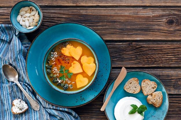 Teller mit frischer hausgemachter kürbiscremesuppe mit samen und toast mit herzform