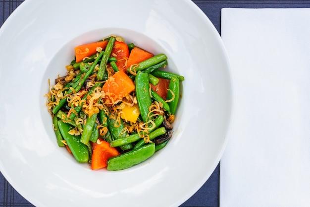 Teller mit gebackenen grünen bohnen gemischt mit erbsenschoten und karotten.