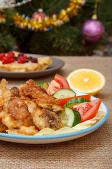 Teller mit gebratenen fischstücken und frisch geschnittenen tomaten und gurken, zitronenscheibe am feiertagstisch mit weihnachtstannenbaum mit spielzeugbällen und girlanden im hintergrund.