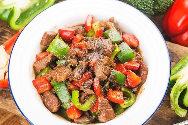 Teller mit gebratenen rindfleischwürfeln mit grünem pfeffer