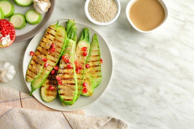 Teller mit gegrilltem gemüse und leckerem tahini auf dem tisch, draufsicht