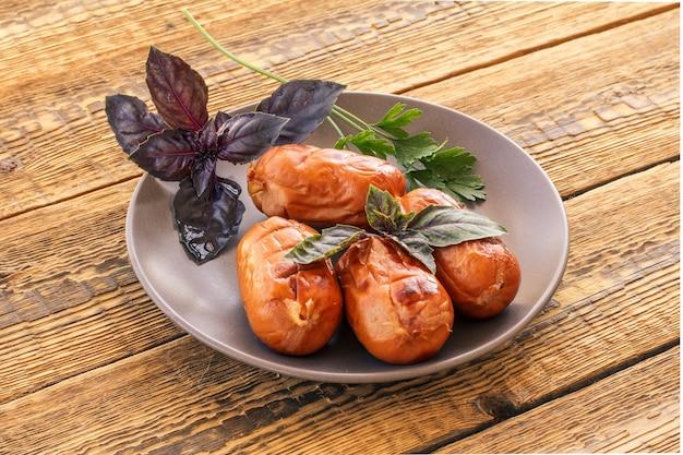 Teller mit gegrillten würstchen, petersilie und basilikum auf alten holzbrettern.