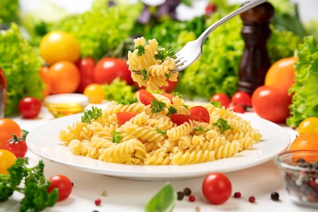 Teller mit gekochten italienischen fusilli-nudeln auf einer gabel mit tomaten und basilikumblättern