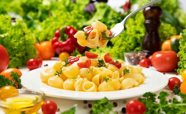 Teller mit gekochten italienischen nudeln, pipe rigate auf gabel mit tomaten und basilikumblättern