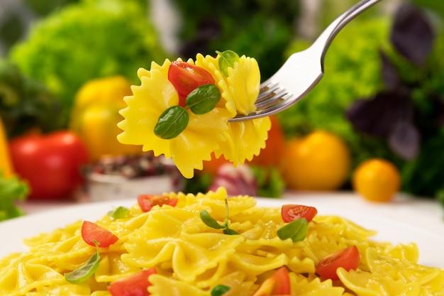 Teller mit gekochten italienischen pfeifen-rigate-nudeln mit tomaten und basilikumblättern mit viel essen