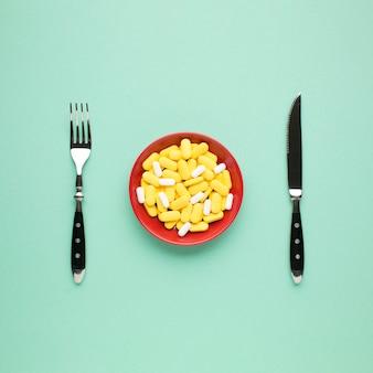 Teller mit gelben und weißen pillen mit besteck auf grünem hintergrund
