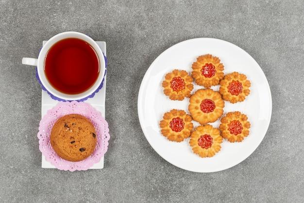 Teller mit gelee-keksen mit einer tasse tee und einem chip-keks