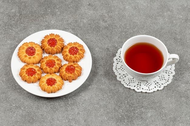 Teller mit geleekeksen und tasse tee auf marmoroberfläche