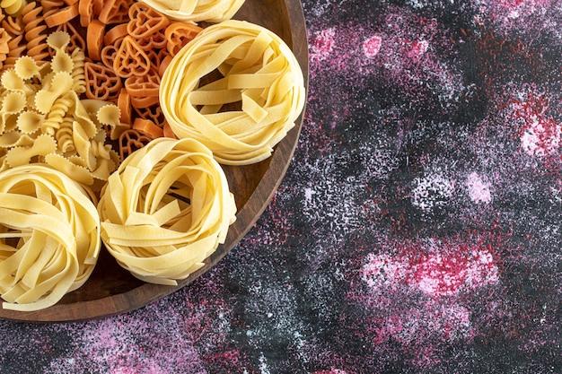 Teller mit gemischten rohen makkaroni.