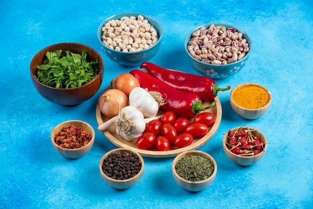 Teller mit gemüse, bohnen und gewürzen auf blauem hintergrund.