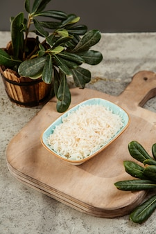 Teller mit geriebenem käse auf dem schneidebrett