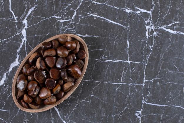 Teller mit gerösteten essbaren edelkastanien auf marmor.