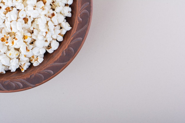 Teller mit gesalzenem popcorn für filmabend auf weißem hintergrund. foto in hoher qualität