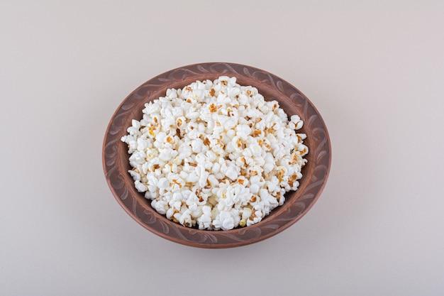 Teller mit gesalzenem popcorn für filmabend auf weißer oberfläche. hochwertiges foto