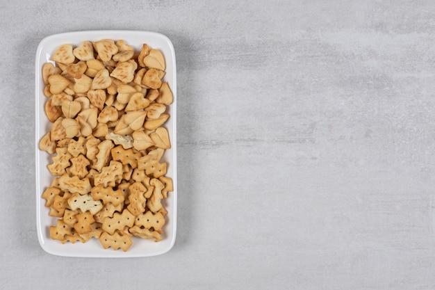Teller mit gesalzenen crackern auf stein.