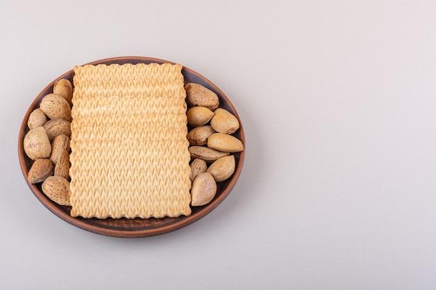 Teller mit geschälten bio-mandeln und keksen auf weißem hintergrund. foto in hoher qualität