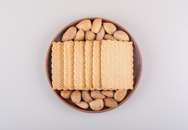 Teller mit geschälten bio-mandeln und keksen