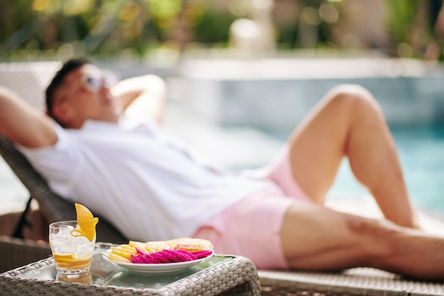 Teller mit geschnittenen früchten und gläsern gin tonic mit range peel auf dem tisch neben dem mann, der auf der chaiselongue ruht