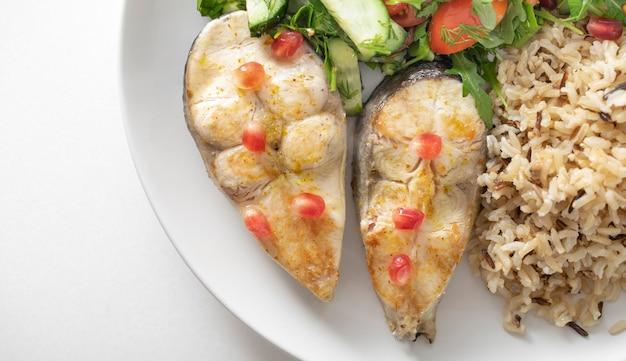 Teller mit gesundem essen, gebratene forelle. wilder vollkornreisbrei und salat.
