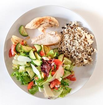 Teller mit gesundem essen. wildreis, gekochte hühnerbrust und verschiedene gemüsesorten in einem salat.