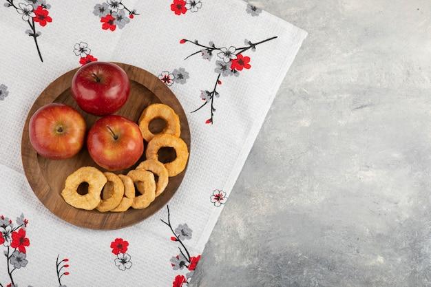 Teller mit getrockneten apfelringen und frischen roten äpfeln auf weißer tischdecke.
