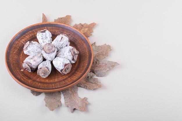 Teller mit getrockneten kakis und trockenen blättern auf weißem hintergrund. foto in hoher qualität