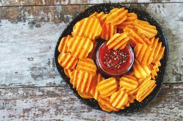 Teller mit gewürzsauce und gewellten kartoffelchips. ungesundes essen. amerikanischer snack.
