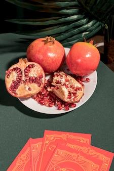 Teller mit granatäpfeln neben tarotkarten