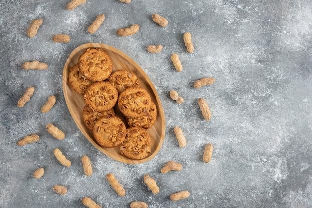 Teller mit hausgemachten keksen mit bio-erdnüssen auf marmortisch.