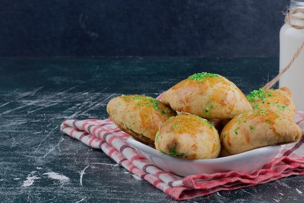 Teller mit hausgemachten keksen und glas milch auf marmortisch.