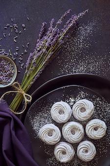 Teller mit hausgemachten marshmallows (zephyr, baiser) mit lavendel auf dunkel gemacht
