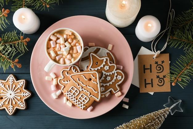 Teller mit hausgemachten weihnachtsplätzchen, kaffee, marshmallows auf holztisch, auf blau. draufsicht