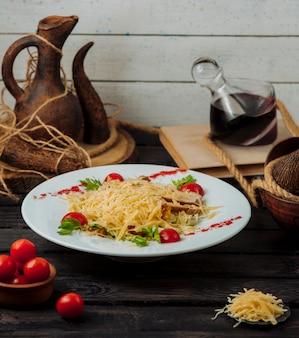 Teller mit hühnchen caesar salat mit geriebenem parmesan an der spitze