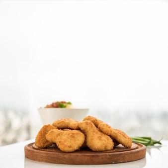 Teller mit hühnerstücken auf umhüllungsbrett