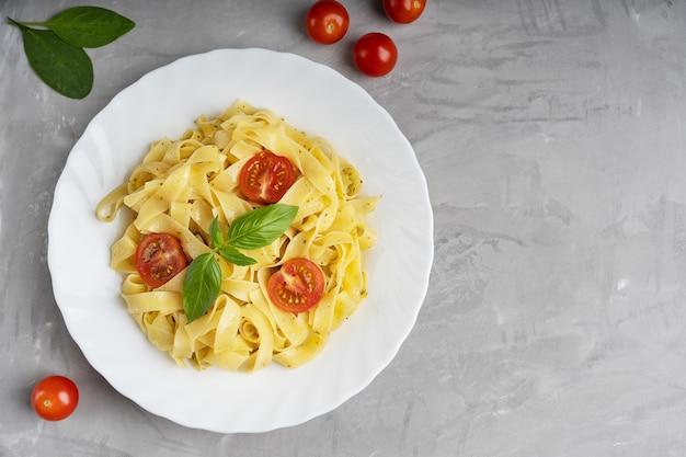 Teller mit italienischen fettucine-nudeln mit basilikumblättern und tomaten auf grauer betonoberfläche. draufsicht